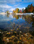 Fall colored trees and snow dusted durnes that the mouth of Miner's River in Pictured Rocks National Lakeshore, MI