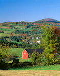 Farms nestled in a valley of green pastures and autumn colored hardwood forests near Peacham in Caledonia County, VT