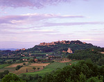 Tuscany, Italy:  Evening light on the hill town of Montepulciano and Chiesa San Biagio with the scattered farms and fields of the Val d'Orcia