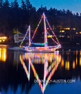 Vashon Island, Washington: Christmas lights illuminate a sailboat on Quartermaster Harbor at dusk