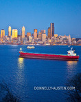 Seattle, Washington: Dusk on Elliott Bay with red container ship and passing ferry boat with Seattle city skyline glowing in reflected light