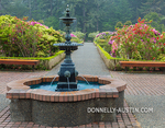 Shore Acres State Park, OR: The Simpson Estate garden with fountain in the center of the pathway in spring featuring azaleas and rhododendrons in bloom.