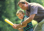 Father and young son practicing with a baseball bat.