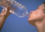 Female athlete drinks from water bottle.