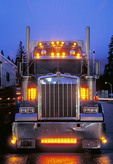 Semi truck with lights on at dusk