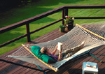Man in hammock on back deck reading.