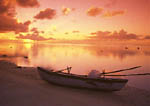Dug-out canoe at sunset on tropical island