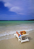 Woman on the beach relaxing in a chair