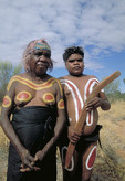 Aboriginal boy and grandma in paint hoding boomerang