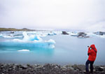 Tourist viewing iceburgs in Iceland