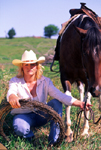Cowgirl mending fence on the range
