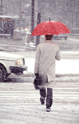 Man with red umbrella in snow storm in Cleveland, Ohio USA