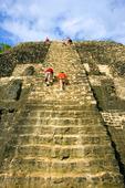 Tourist climbing Mayan ruins at Lamanai