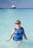 Woman at Half Moon Cay, Bahamas Caribbean beach standiing in ocean with Holland America ms Veendam cruise ship in background
