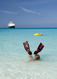swimmer with water fins at Half Moon Cay, Bahamas, beach with Holland America cruise ship ms Veendam in background