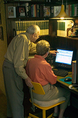 Old man and woman looking at compter monitor with man pointing at screen