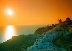 Orange sunset at Oia, Santorini showing Mediterranean Sea and windmills