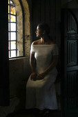 Dominican Republic Woman wearing white dress seated in Window of Fort Ozama