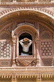 Indian man in window of Fort Palace in costume