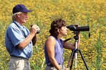 Bird watchers in a field of flowers