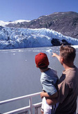 Father and son looking at glaciers on Alaskan cruise ship