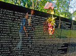 Flag and flowers on the Viet Nam Memorial wall with reflection of people walking past.