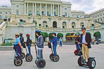 A tour group using a Segway human transporter electric scooter in front of the Capitol building