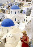 Woman Tourist along White Buildings of Oia in Santorini Greece