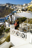 The beautiful white buildings on the mountain cliffs of main city of Fira and romantic couple relaxing on terrace