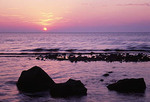 The sun sets over the rocky shore of Lake Michigan, casting pink and purple colors across the sky.