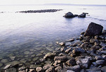 Shallow water washes over rocks on a Lake Michigan shore in late afternoon light at Peninsula State Park.