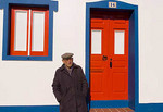 Local man in hat in front of a colorful red door and a window in the beautiful Algarve village.