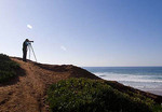 Lone woman photographer with tripod taking pictures of beautiful waves breaking at the Western coast.