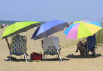 People relaxing on a beach under colorful umbrellas.