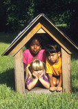A fun shot of mixed race children in the doghouse.