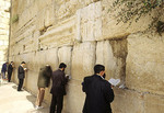 Religious worshipers practicing their religion and chanting and reading at the famous Western Wailing Wall in Jerusalem Israel with prayer messages in cracks.
