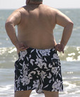 A chubby guy in black and white swim suite on a beach.