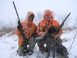 Two hunters with rifles and a dog in orange coats posing for the picture in the snow.