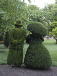 Green male and female figures in a topiary garden.