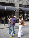 A group of young African American people walking on the street, listening to music and texting.