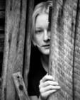 A teenage girl in doorway looking out.