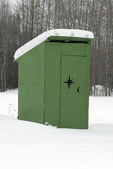 Green outhouse covered in snow in Wiseman, Alaska.