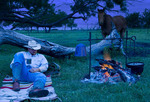 A cowboy relaxing by a campfire at night with his horse.