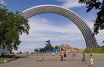 People relaxing in a park with Rainbow Arch in downtown Kiev, Ukraine.