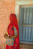 Colorful portrait of a woman in red sari against school wall near Jodhpur in Rajasthan, India.