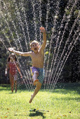 Boy jumps through lawn sprinkler.