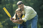 Father  helps daughter learn baseball.