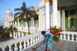 A woman sweeps the floor in the Lalith Mahal Palace hotel, India.