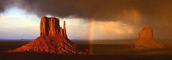 A rainbow forms during a rain and hail storm at sunset between the Mittens in Monument Valley.