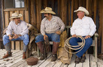 Cowboys relax and talk on an old porch at the ranch.